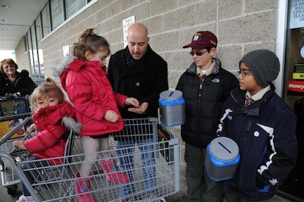 Mark Lubrano, center, and his daughters Kaitlyn, 1, and Brianna, 4, made a donation to Boy Scout Troop 109's food drive outside King Kullen on Dec. 1 which was graciously accepted by Joseph Cavataio and Jonathan Prashad.