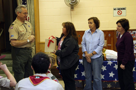 Retiring Scout Master Joe Trimboli, far left, got a surprise from Patti Walsh, Ginny Conway and Mary Rose Bosco.