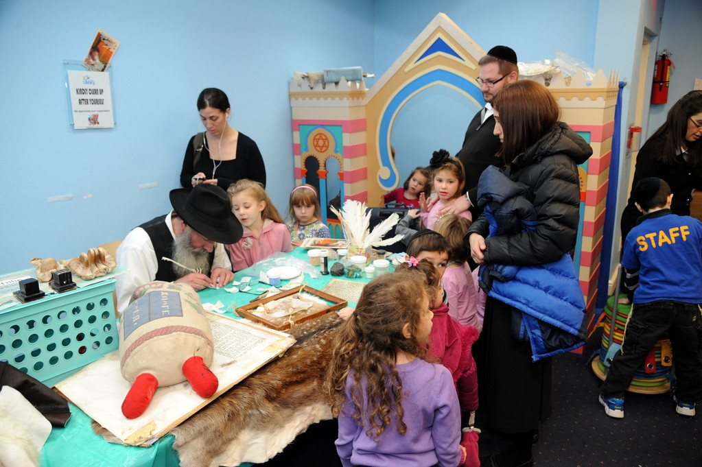 Rabbi Yehuda Clappman helped children with one of the creative activities at the library�s celebration event.