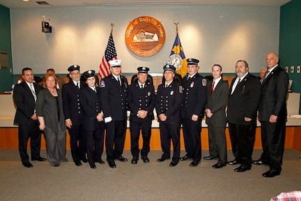 Cited for their brave acts, 13 Rockville Centre firefighters ­— above, with village officials — and police officers were presented with medals on Monday. They helped save four residents from a July house fire.