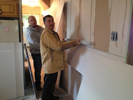 John Reese and Tony Gerrato, of the Make it Count Foundation, work to repair the home of a Baldwin resident.
