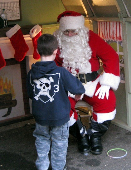 A boy gives santa his Christmas wish list.