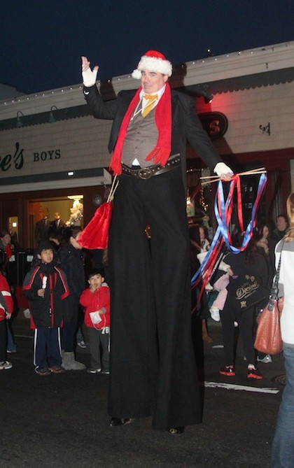 A man on stilts from Clown Magic party Entertainment rose head and shoulders above the crowd.