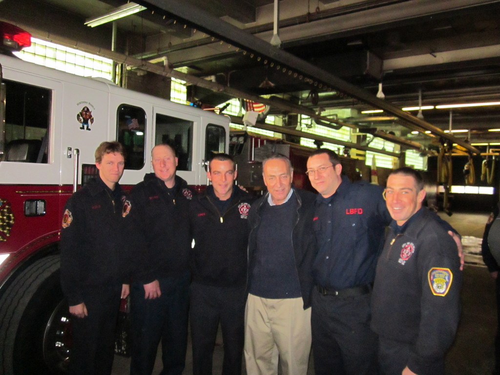 Firefighters Chris Koehle, left, Alex Sharpe, Bryan Jones, Sen. Charles Schumer, Mike Seemann and Brian Olson at last Saturday's press conference, where Schumer announced a grant to rehire the five firefighters.