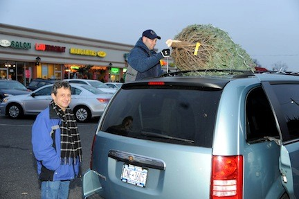 Jonathan Klein looked on as East Meadow firefighter John McGee loaded a Christmas tree onto his car.