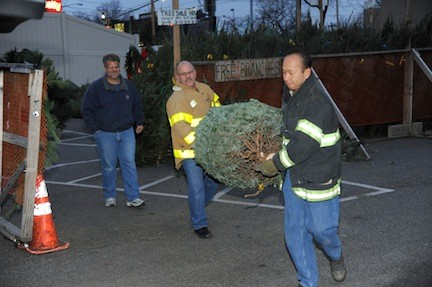 Vinny Nocella watched as East Meadow Fire District volunteers carried a Christmas tree to his car.