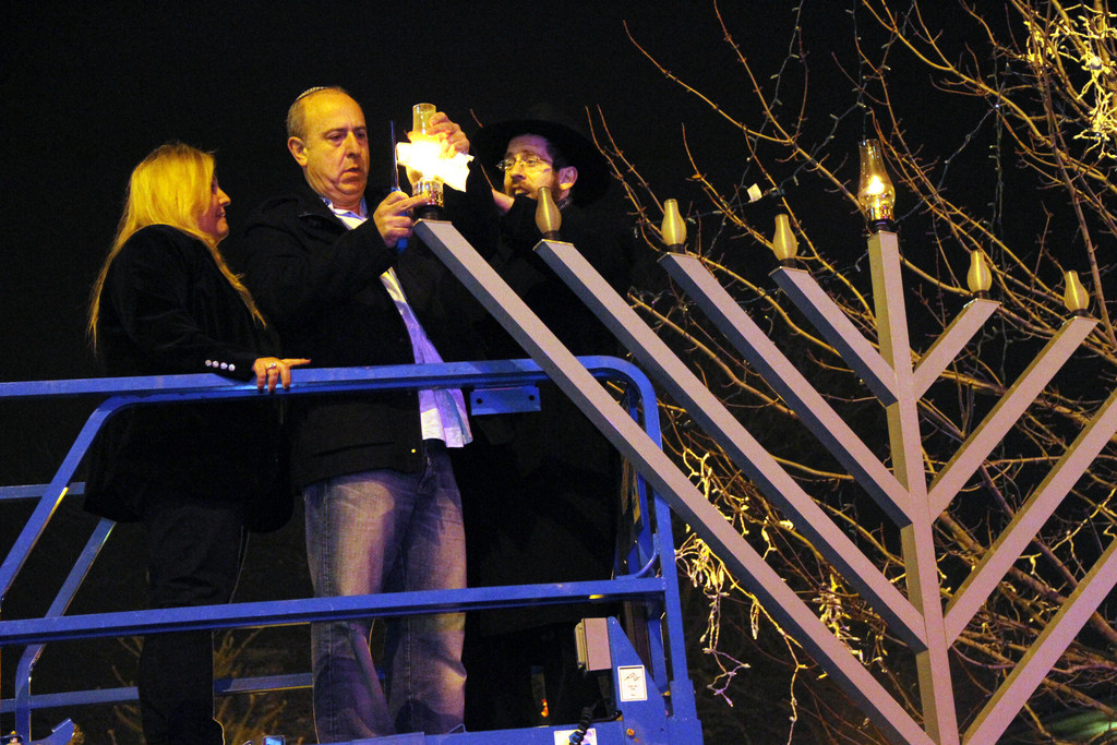 Cindy and Lawrence Knoll, along with Rabbi Shimon Kramer, lit the menorah at the Merrick Long Island Rail Road station.