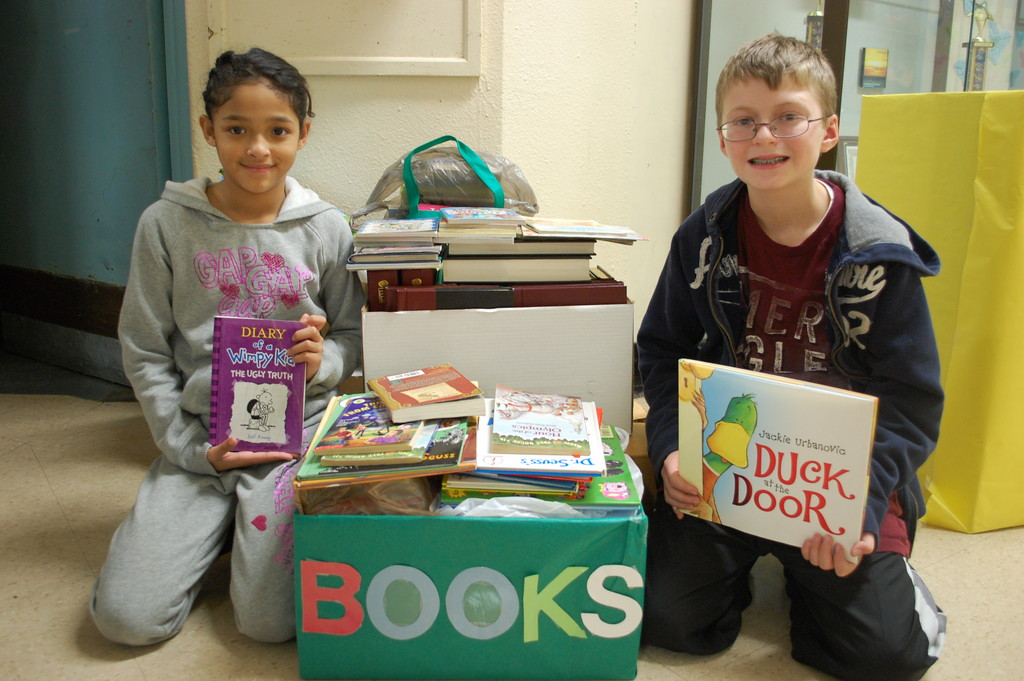 Wheeler Avenue students Isabella Chungata and Michael Ott show some of the books that have been collected to give to schools damaged by Hurricane Sandy.