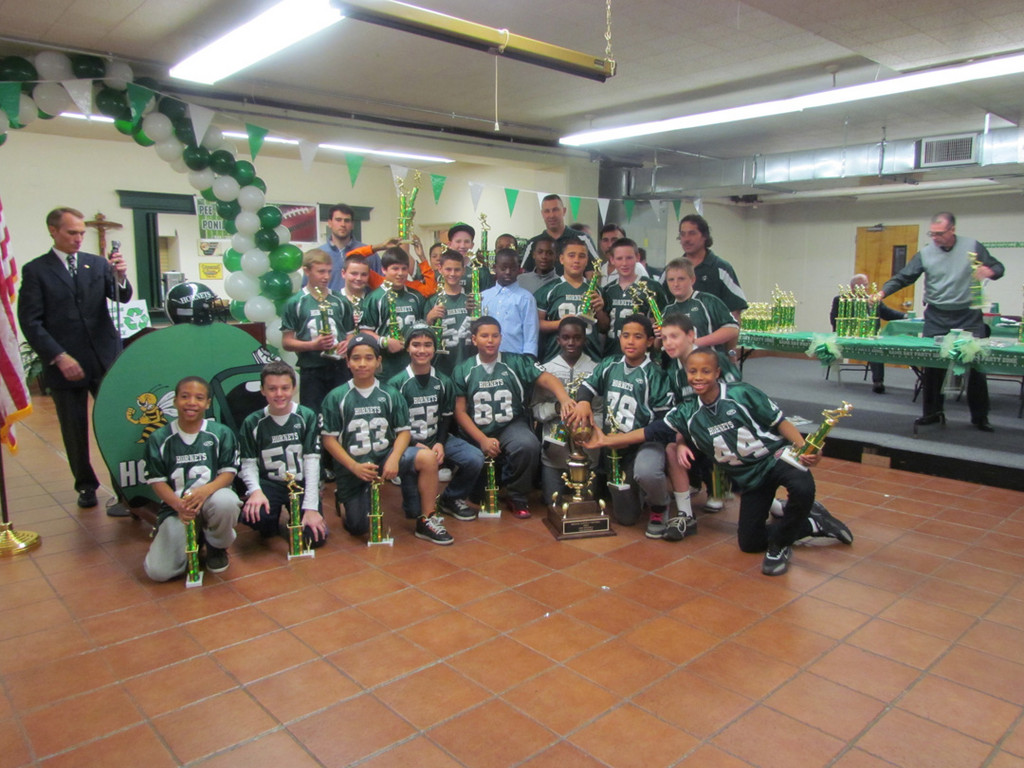 The Pony Green team won the Superbowl in its division. Coach Bill Hughes and coordinators Scott Heuer, Frank Agueros, Mike Cruz and Blaise Ancona proudly stand with their players.