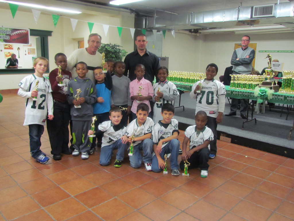 The Pee Wee White team of the Green Hornets collected their trophies at the Blessed Sacrament Church. Coach Dan Moran and defensive coordinator Eric Ottochian stand with their team.