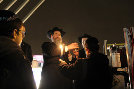 Rabbi Ytzchak Goldshmid prepares a blessing while his son holds the candle.