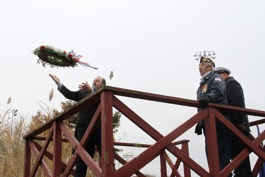 Mayor Murray tosses the wreath into the Mill River as George Antonucci and Jack Gallagher look on.