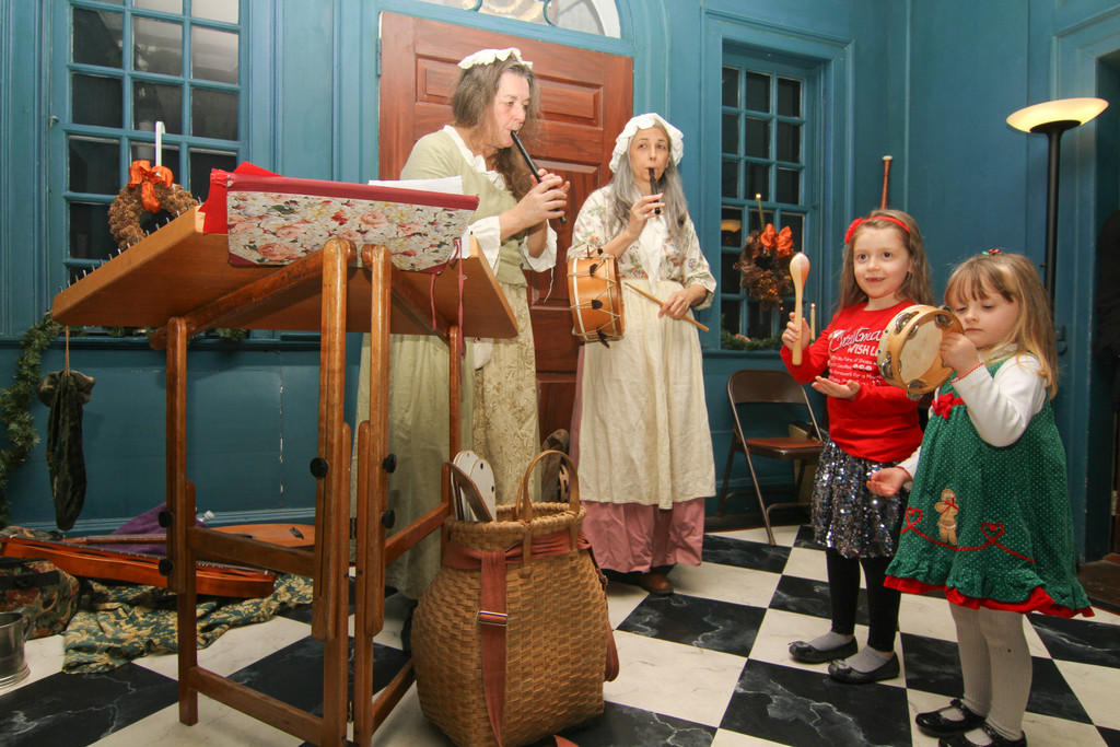 Colonial-style Christmas music was performed by Linda Russel and Christa Patin, at left, with assistance from sisters, Laura, 6, and Lillie, 4, Lederer.