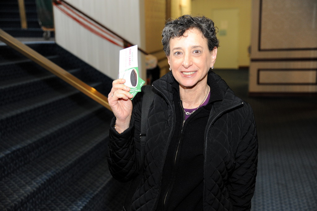Joan Kavarsky shows off the two Dunkin' Donuts vouchers for a medium- sized coffee after she donated blood.