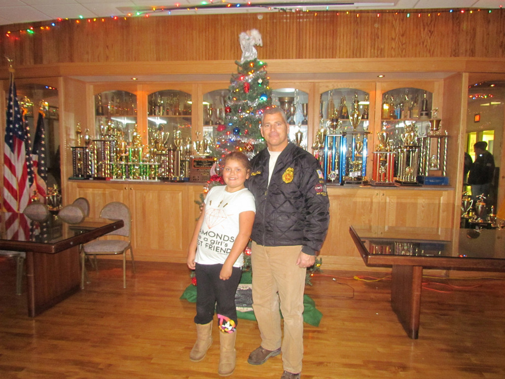 Elizabeth Torres, 8, with Chief Chris Gioia at the tree lighting at the Franklin Square/Munson firehouse.