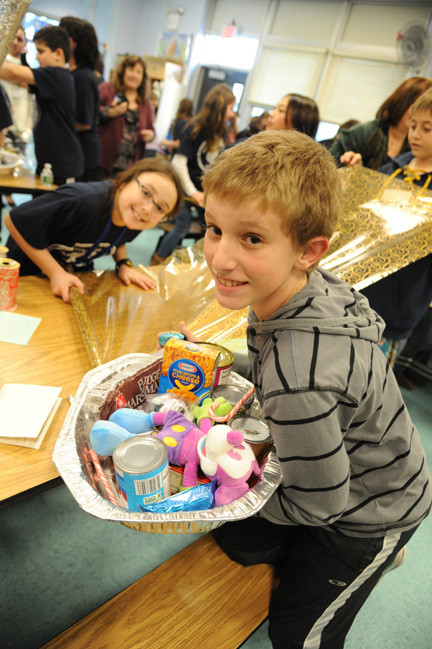 Joe Sena, of Oceanside, and Morgan Aimes, from the Seaford-Oyster Bay School District, worked together packing baskets of food and goods for Oceanside families at School 4 earlier this week
