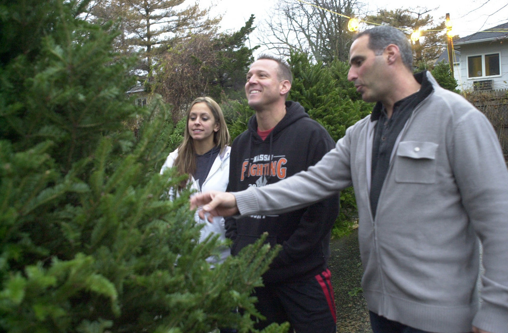 Merrick fire volunteer Ron Luparello, front, showed a Christmas tree to Bill and Selena Iger of Bellmore at the Merrick Fire Department's annual Christmas tree and wreath sale. The Igers bought the tree.