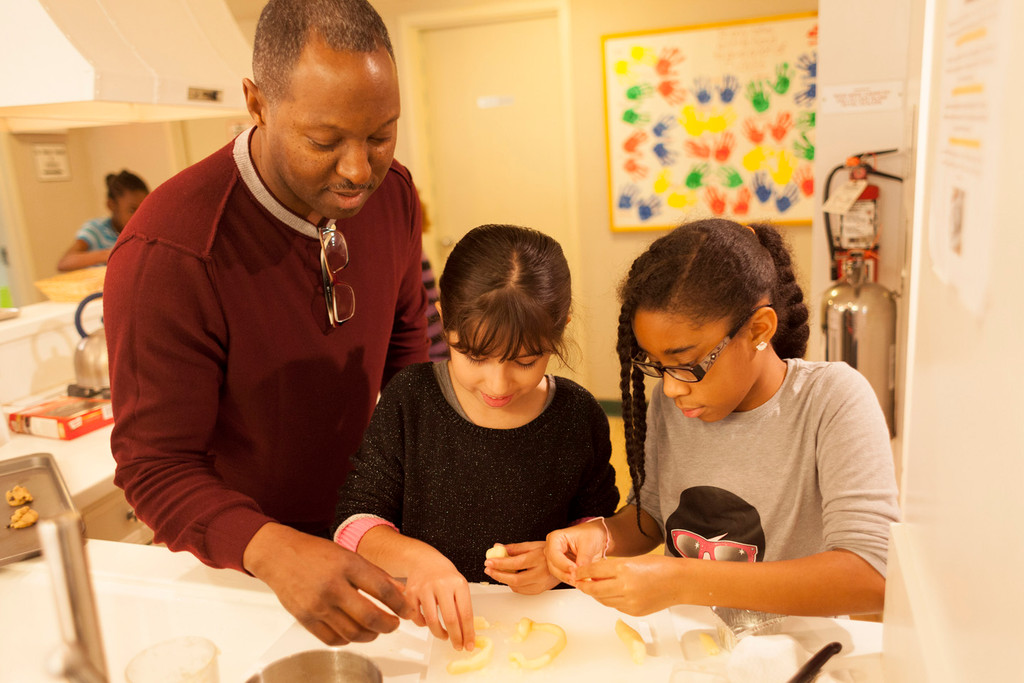 John Singleton, principal of Clear Stream Avenue School, helps students Sofia Pereyra and Gabrielle Delwin bake for families at the Ronald McDonald House.