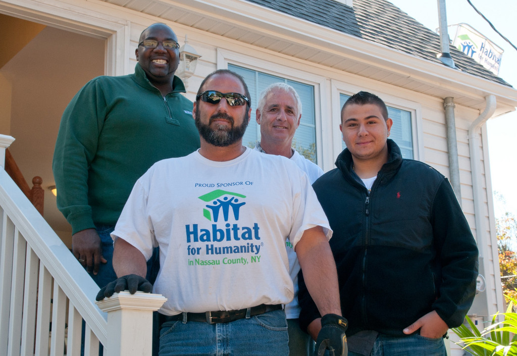 Standing on the finished house's porch were, in back, from left, Barry Tech Principal James Clark, Nassau County Habitat for Humanity Vice President Tom Baccarelli, Nassau BOCES Vice District Clerk Michael Weinick, and Lynbrook High School and Barry Tech student Giuseppe Condeleo.