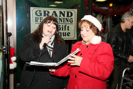 Viki Sorrentino, left, sany Christmas carols outside Dear Little Dollies at the shop's holiday event on Dec. 7.
