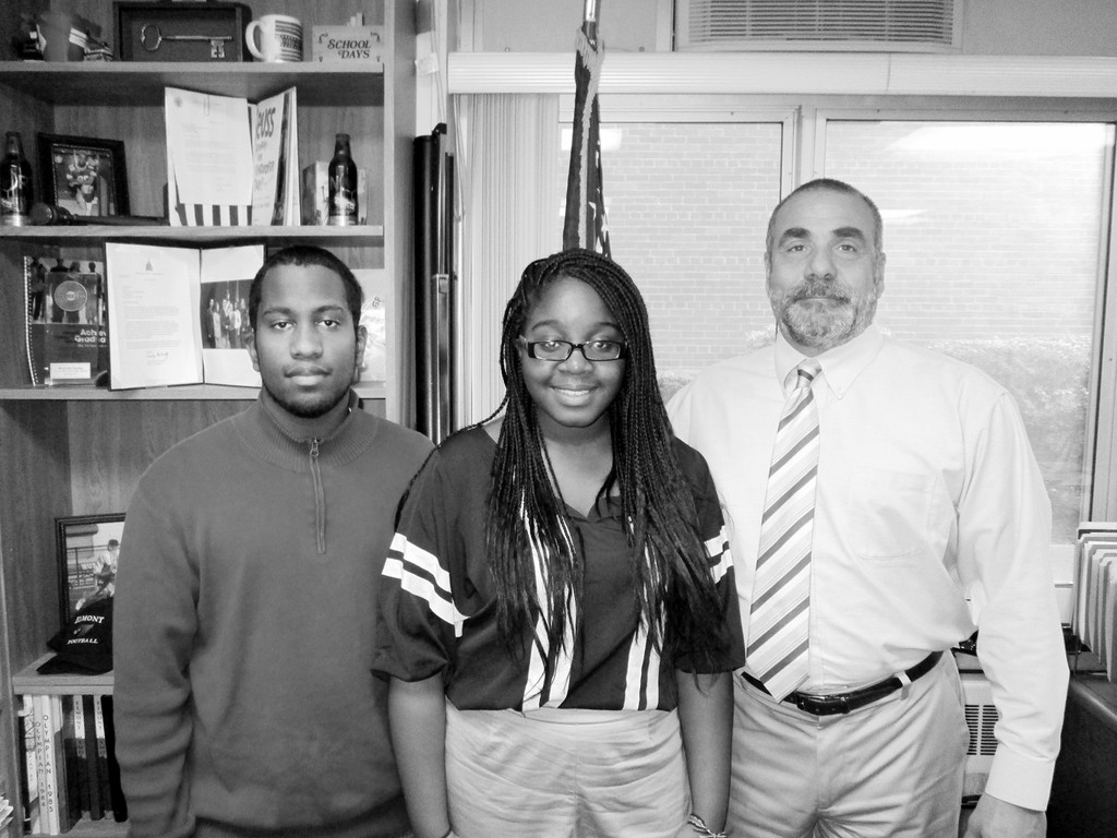 Elmont seniors Andrew Eccles and Chidinma Nwaogbe with principal John Capozzi.