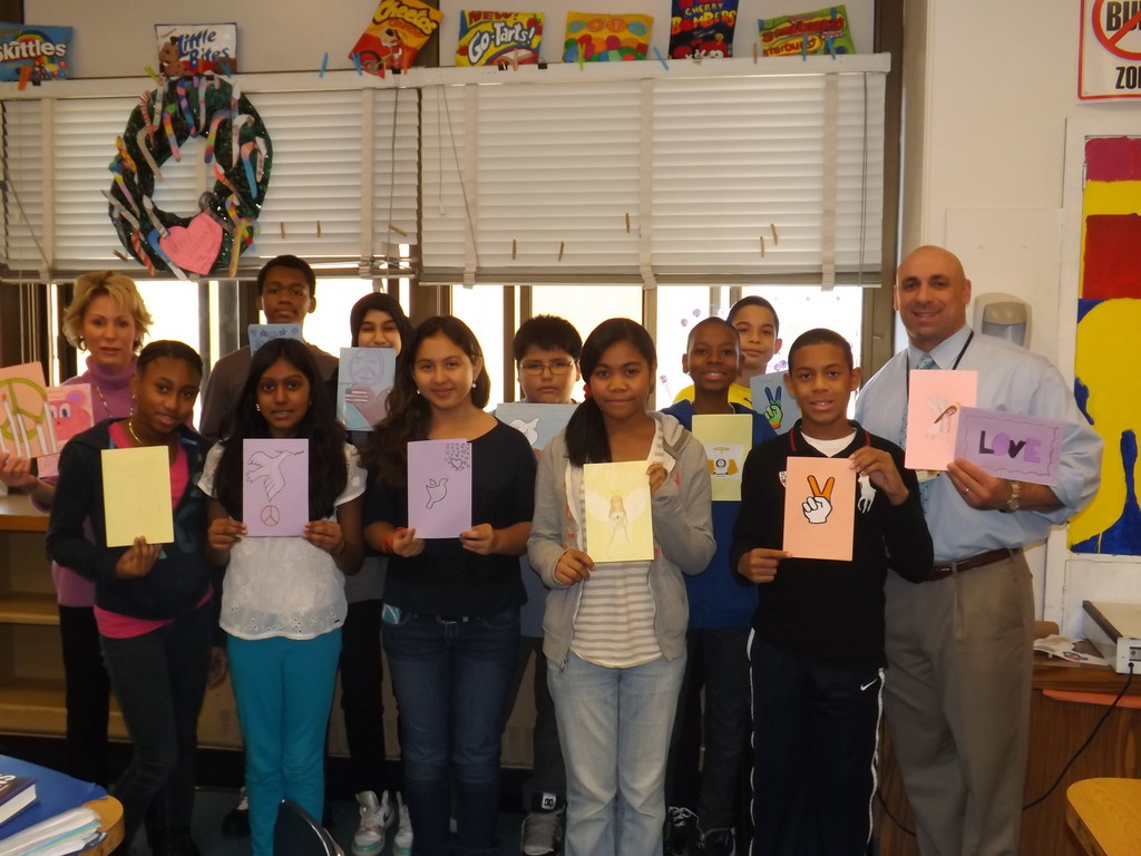 Students in Lynne Pravda's art classes at Memorial Junior High School made cards for the people of Newtown, Conn. to show their support of the grief-stricken community. Pictured with Pravda, top left, are a group of seventh graders displaying their work and Memorial Principal Anthony Mignella, right.