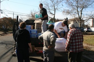 Peter Visconti, standing, and Felipe Plaza, both of the Five Towns Community Center, handed out food, water and supplies to Hurricane Sandy victims on Cheshire Road in Inwood on Nov. 12.