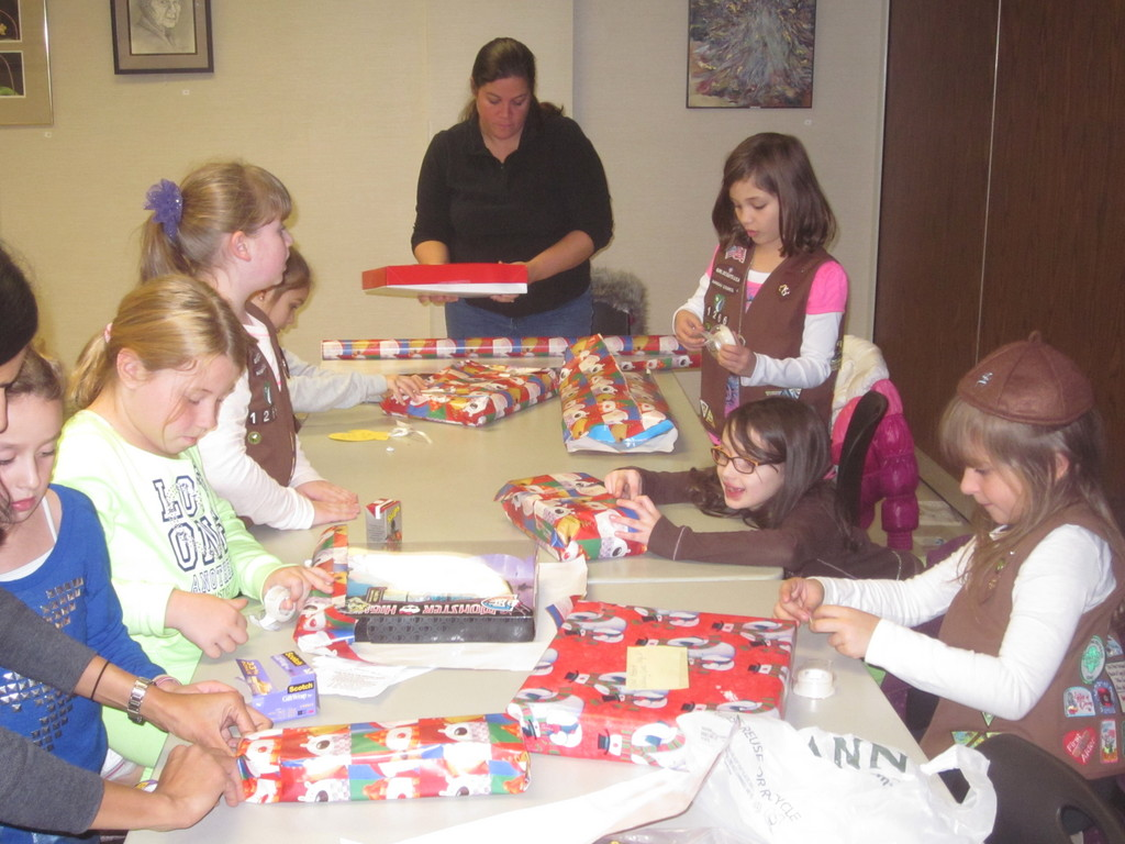 The two Girl Scout troops spent their evening wrapping the toys to give to kids.