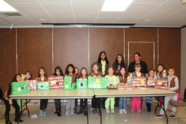 The 7 and 8-year-old girls of the East Meadow Girl Scouts Troops 1266 and 1674 gift wrapped presents for Hurricane Sandy victims. Also pictured are troop leaders, top row, left to right, Ganga Visvanathan, Christin Medina and Kathy Columbia.