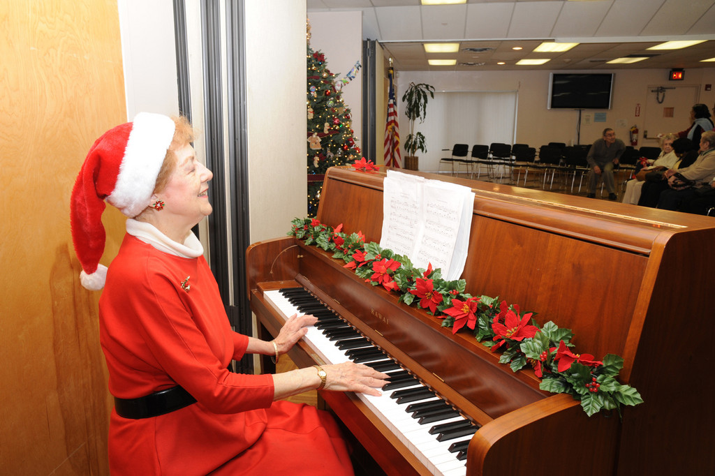 Pianist Betty Bergbuchler played a piano joyfully at the holiday party on Dec. 20 at the Sandel Center.
