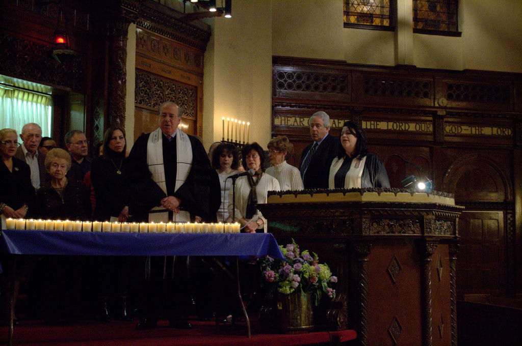 Rabbi Jay Rosenbaum, center, led Temple Israel congregants in prayer after all 26 candles were lit.