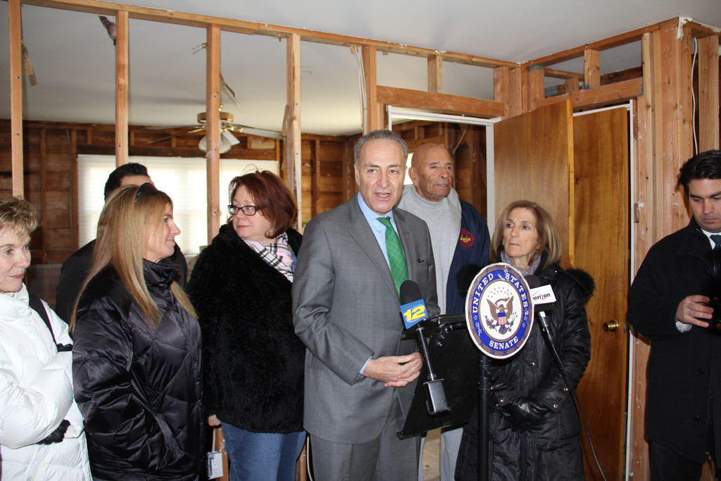 Sen. Chuck Schumer held a press conference on Wednesday at the storm-ravaged home of Councilwoman Fran Adelson, far right, where he criticized House Speaker John Boehner and other Republicans for failing to pass a Senate-approved $60.4 billion Hurricane Sandy relief package.