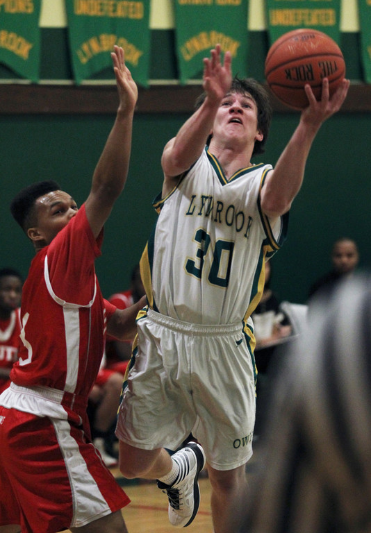 Lynbrook's Matt Murphy, right, makes an aggressive move to the basket during last Friday's hard-fought overtime loss to Valley Stream South.
