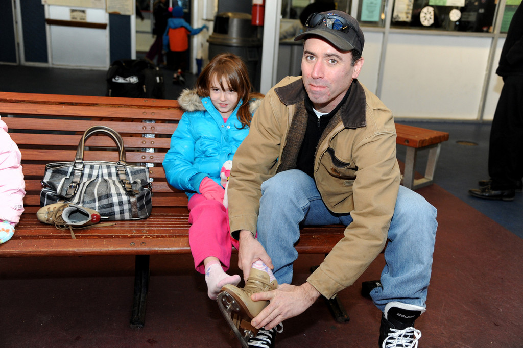 John Minogue, right, helped his 7-year-old daughter, Brooke, put on her skates.