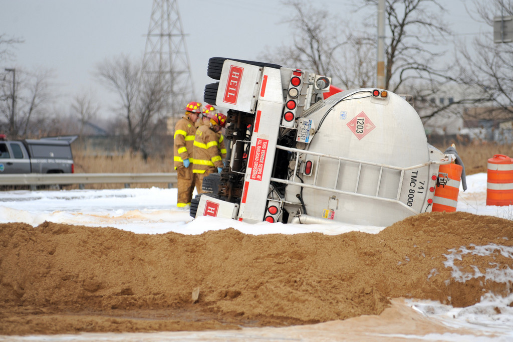 Firefighters at the scene of the truck overturn examine the vehicle.