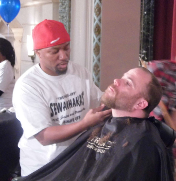 Organizer Rob Anderson gets his beard trimmed for charity.
