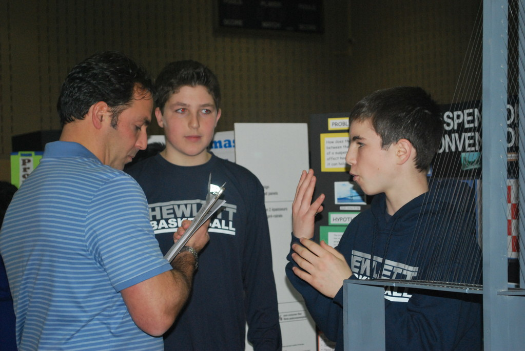 Woodmere Middle School science teacher Scott Zanville, left, spoke to students Zach Bromfeld, center, and Kyle Hoberman about their suspension bridge project.