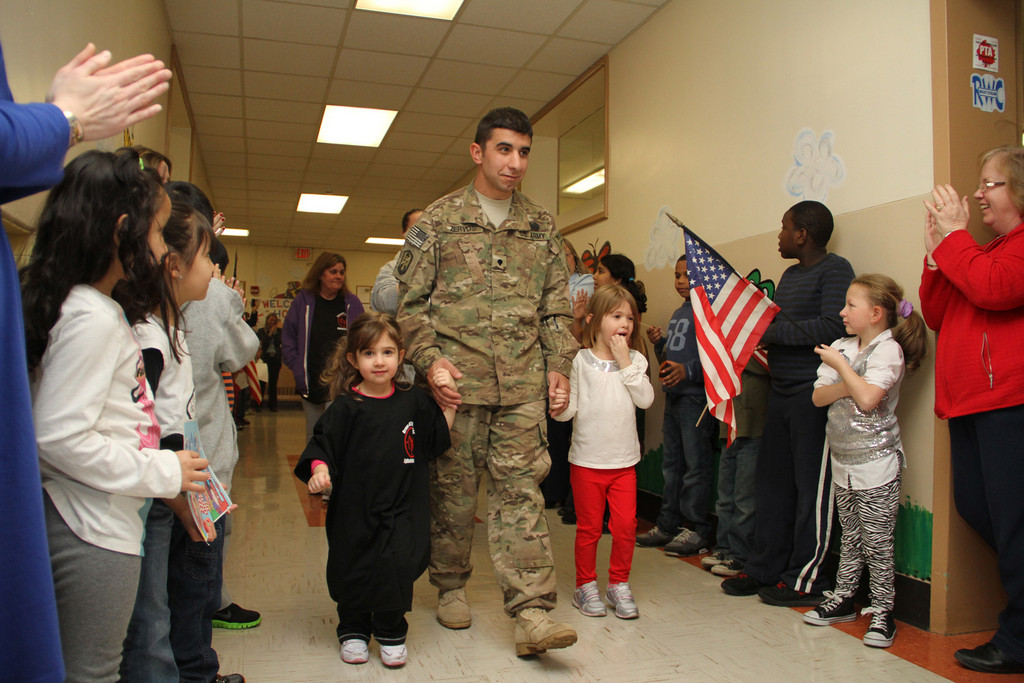 Spc. Michael Zervos, flanked by his daughters Alexandra and Danielle, walked down the hallway while the entire school saluted and applauded him.