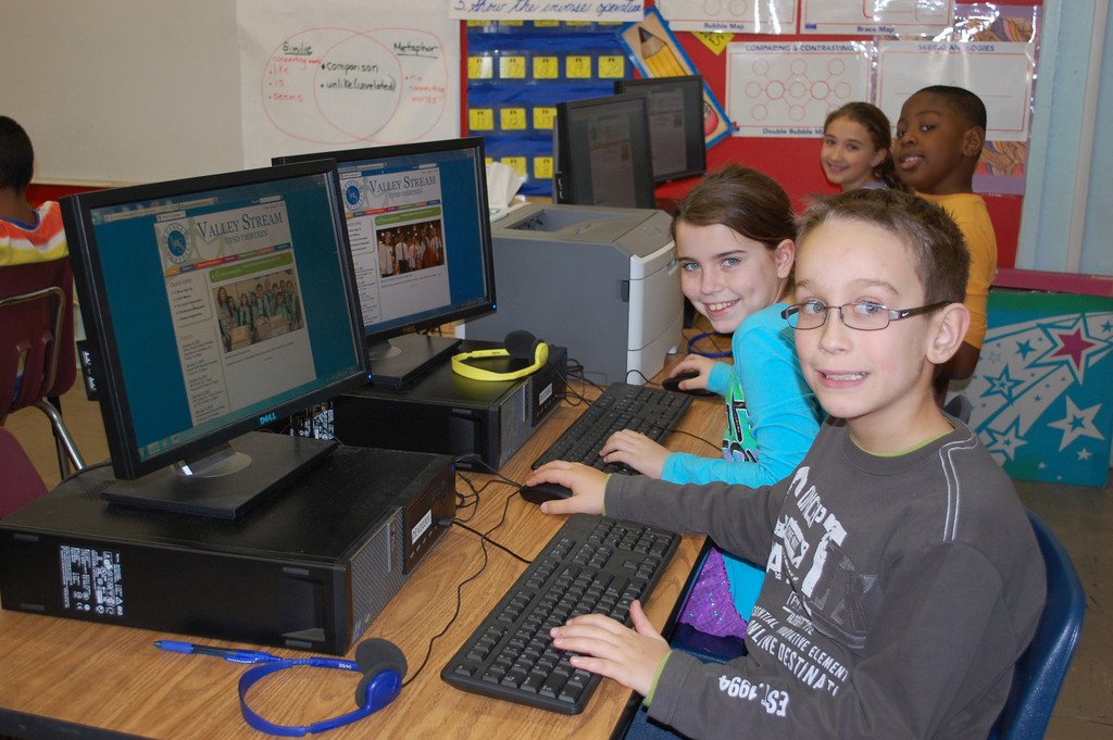 James A. Dever School students, from left, Lucas Almeida, Hailey Danna, Ralph Destin and Jenna Campo use the new District 13 website.