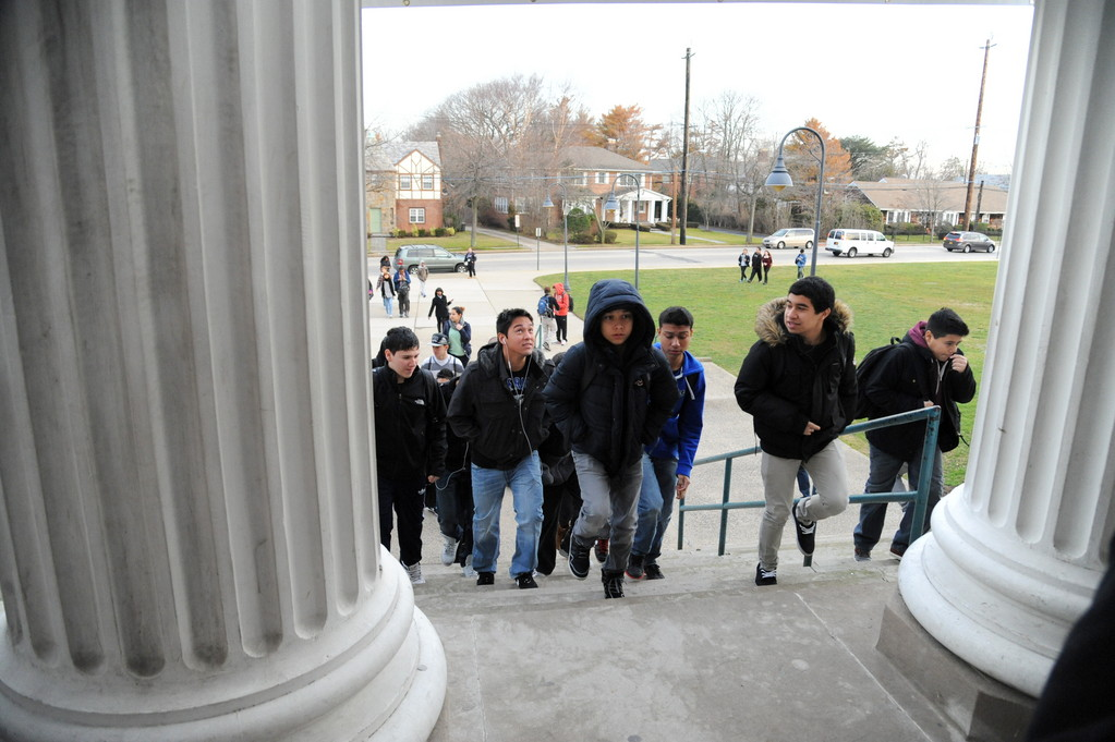 High school students walked up the stairs and through the columns of the middle school before they entered the building.