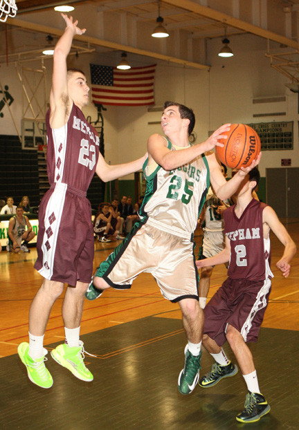 Kennedy's Tyler Merron, center, attacked the basket with Mepham's David Gilroy, left, and Brian Keohane defending during last Friday's game.