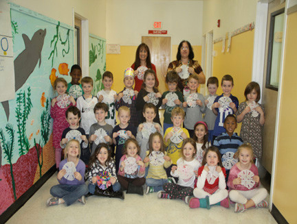 Teaching assistant Anita Roseman (top left), teaching aide Doreen Farano (top right) and students in Patrice Camastro's kindergarten class proudly displayed their snowflakes before sending them off to Sandy Hook Elementary School.
