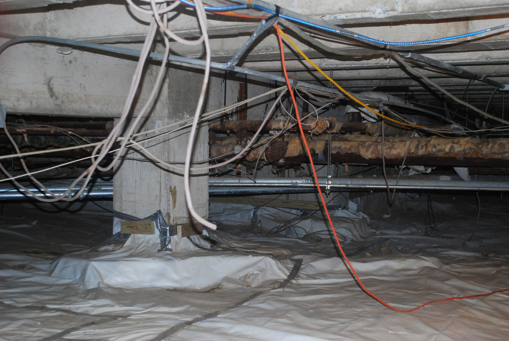 After Hurricane Sandy, the crawl space under Lawrence High School had to be cleaned and leveled. Now repair of the electrical system is being performed.