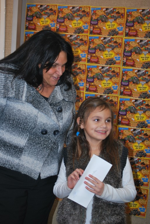 Isabella Andrarde, right, won one of the two grand raffle prizes of four tickets to see the monster trucks at Nassau Coliseum. At left, Carolynn Matulewicz, Peninsula Public Library�s children�s librarian.