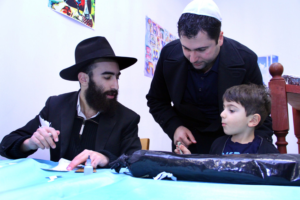 Chabad of Hewlett completed the year-long task of writing a new Torah. Voazdavid Bitton wrote Liam Narkis' name on a scroll while dad, Chaim, watched.