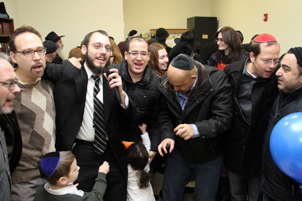 Rabbi Nochem Tenenboim, with microphone, led Chabad members in dance to celebrate the completion of the Torah writing.