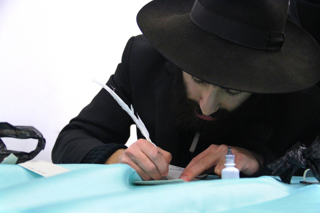 Scribe Voazdavid Bitton brought surgeon-like intensity to his work of writing names on the scrolls of the new Torah.