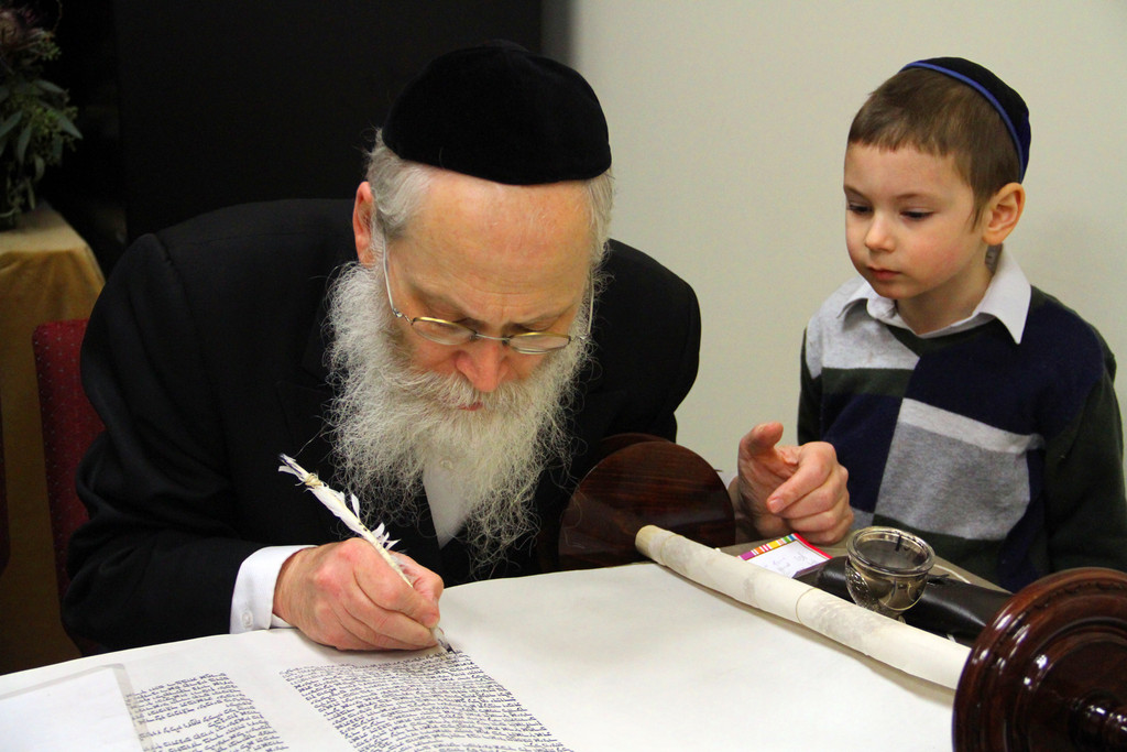 Chabad of Hewlett marked the year-long completion of writing a new Torah last Sunday. Yossi Tenenboim watched Rabbi Moshe Klein finish a scroll.