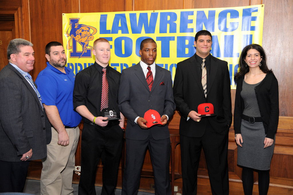 Three Lawrence High School seniors signed their national letters of intent to attend and play football at three different Division I schools. From left were, Assistant Superintendent Pat Pizzarelli, football coach Joe Martilotti, students Eddie Robinson, Tyler Fredericks, Islam Mohamed and high school Principal Dr. Jennifer Lagnado.
