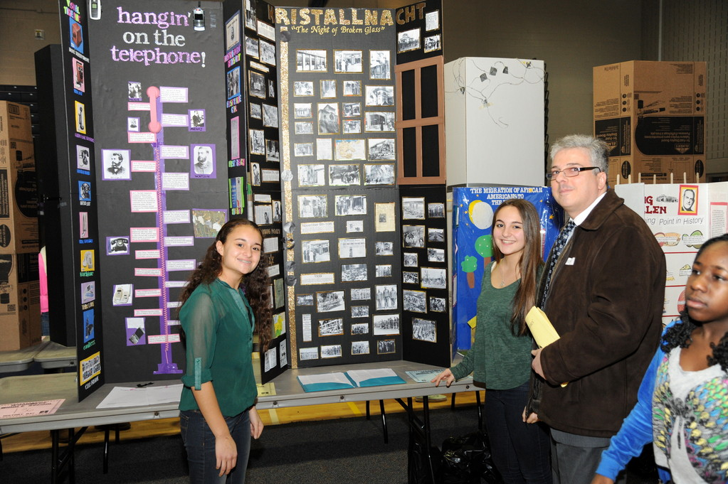 Woodmere Middle School�s History Fair had students creating a variety of projects about past events. From left were, Dana Feldman and Louisa Evola, who showed their Kristallnacht project to Louisa�s dad, Sal Evola.